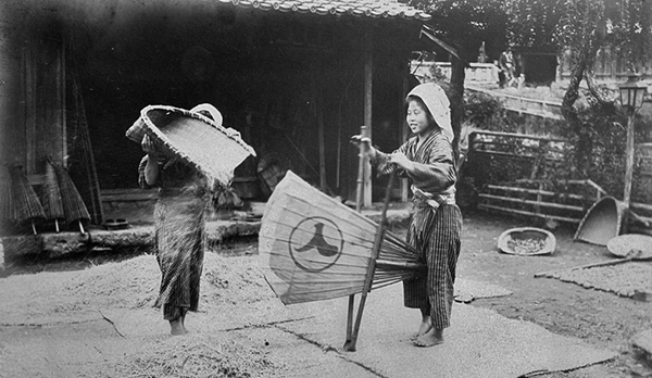 black and white photo of 2 Japanese women using winnowing baskets